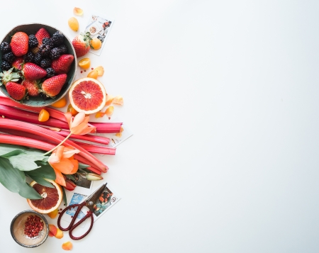 fruit flatlay featuring berries, grapefruit, rhubarb and flowers