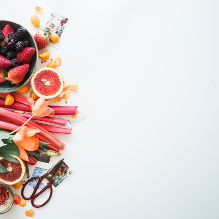 fruit flatlay featuring berries, grapefruit, rhubarb and flowers