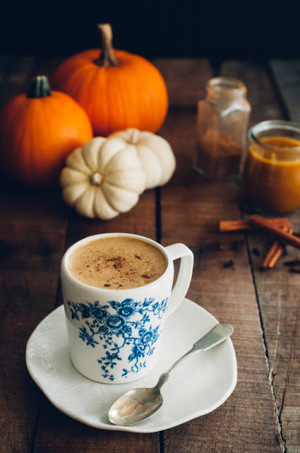Cup of AIP compliant spiced pumpkin latte with pumpkins and spices in the background on a table