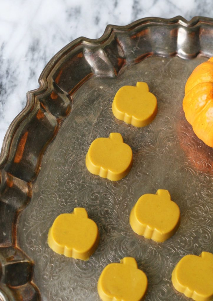 Tray of AIP compliant pumpkin shaped halloween turmeric gummies on a marble counter